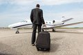 Businessman walking towards corporate jet rear view of with luggage Stock Images