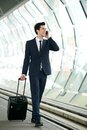 Businessman walking on train station platform and talking on phone portrait of a handsome the Royalty Free Stock Images