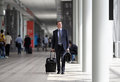 Businessman walking with trolley through the crowd on a business travel Royalty Free Stock Photo