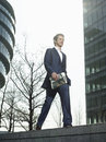 Businessman walking on wall outside office building full length of young with newspaper Stock Photography