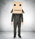 Businessman wearing carton box with drawn emotions Royalty Free Stock Photo