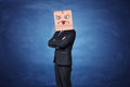 Businessman wearing carton box with painted angry face showing tongue on it Royalty Free Stock Photo
