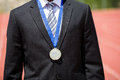 Businessman wearing gold medal mid section of and standing on running track Royalty Free Stock Photos