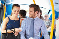 Businessman and woman looking at mobile phone on bus sitting down with passengers in background Royalty Free Stock Photography