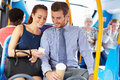 Businessman and woman looking at mobile phone on bus whilst sitting down smiling with passengers in background Royalty Free Stock Images