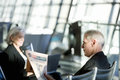 Businessman and woman sitting in airport departure lounge, woman using laptop, man reading financial newspaper, side view Royalty Free Stock Photo