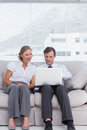 Businessman and woman sitting on couch women using laptop Royalty Free Stock Images
