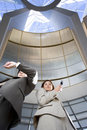 Businessman and woman standing below skylight in airport man checking time on wristwatch woman using mobile phone portrait low Stock Photography