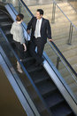 Businessman and woman standing on escalator in airport terminal talking elevated view women Royalty Free Stock Images