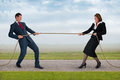 Businessman and woman tug of war businesswoman contest strength Royalty Free Stock Image
