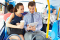 Businessman and woman using digital tablet on bus with holding takeaway coffee Stock Images