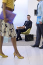 Businessman and woman walking in foyer by businessman in chair with newspaper, low section (blurred motion) Royalty Free Stock Photo