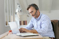 Businessman working with headset on laptop Royalty Free Stock Photo