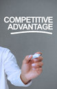 Businessman writing competitive advantage with a marker on grey background Stock Image