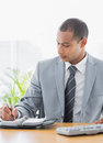 Businessman writing in diary at office desk concentrated young Stock Photos