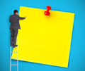 Businessman writing on a giant yellow post blue background Stock Photo