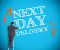 Businessman writing next day delivery on a wall giant blue Stock Photos