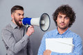 Businessman yelling via megaphone to another man Royalty Free Stock Photo
