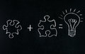 Businessmans Hand drawing puzzle on blackboard to explain business concept. Solving puzzle together. Drawing light bulb on blackbo Royalty Free Stock Photo