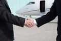 Businessmen handshake in front of a corporate jet shake hands travel Royalty Free Stock Photography