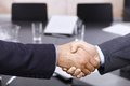 Businessmen handshake over table closeup of hands in office meeting room Royalty Free Stock Photos