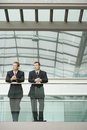 Businessmen looking away while standing against glass railing two in office Royalty Free Stock Images