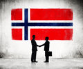 Businessmen with norwegien flag on background two shaking hands as a Stock Photo