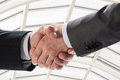 Businessmen shake hands against modern office interior background closeup shot of Stock Photo