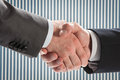Businessmen shake hands against office interior background closeup shot of Stock Image