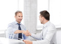 Businessmen shaking hands in office picture of Stock Photography