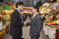 Businessmen shaking hands at street market side view of young Royalty Free Stock Photos