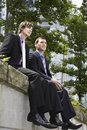 Businessmen sitting on wall outside office low angle view of two young Royalty Free Stock Image
