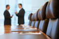 Businessmen talking in conference room side view of two blurred Royalty Free Stock Photos