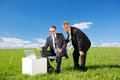 Businessmen two having a meeting with laptop in green meadow Royalty Free Stock Images