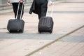 Businessmen walking with wheeled luggage two on city sidewalk Stock Images