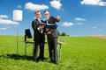 Businesspartners are work in a green meadow two businesspersons with binder pointing on something on under sunny sky Royalty Free Stock Photography