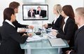 Businesspeople attending video conference at desk in office Royalty Free Stock Images