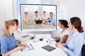Businesspeople attending video conference sitting in room looking at projector screen Stock Photo