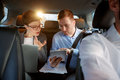 Businesspeople with computer and tablet in car on trip Royalty Free Stock Photo