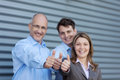 Businesspeople gesturing thumbs up against shutter portrait of happy businessmen and businesswoman Stock Photography