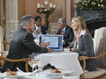 Businesspeople having conversation with laptop two using at restaurant table men in background Stock Photos