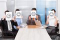 Businesspeople holding smiley icon