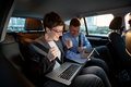 Businesspeople looking at laptop in car on trip Royalty Free Stock Photo