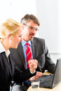 Businesspeople looking at laptop in consultation Stock Image