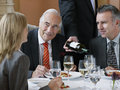 Businesspeople at restaurant table as waiter serves wine three talking Stock Photos