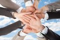 Businesspeople s hands on top of each other symbolizing unity closeup business people against sky Stock Photos