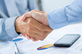 Businesspeople shaking hands close up of at desk Royalty Free Stock Photography