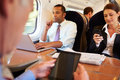 Businesspeople on train using digital devices at table Royalty Free Stock Images