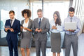 Businesspeople using mobile phone lap top and digital tablet standing in a row in office Stock Photography