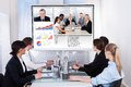 Businesspeople in video conference at business meeting sitting a room looking screen Stock Photo